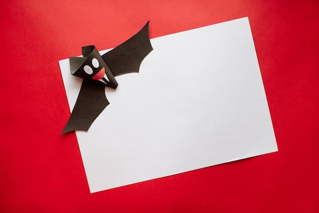 Zabawny Nietoperz Halloween Wykonane Z Papieru Na Czerwonym Tle. Pocztówka Na Helloween Premium Zdjęcia