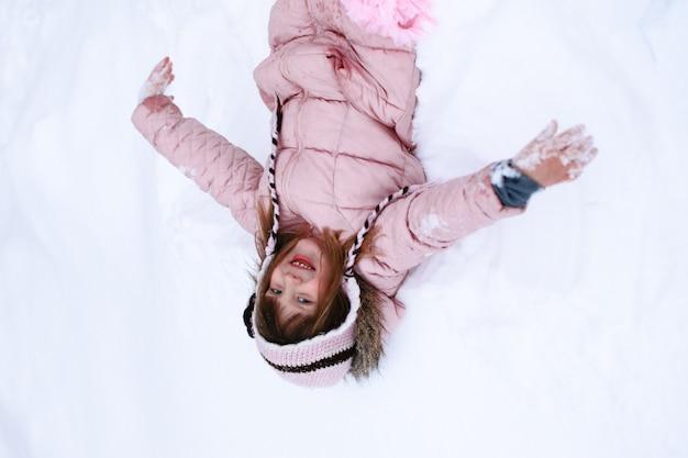 Zabawy Dziewczyna W Różowej Kurtce Delikatnie Marznie Na Zewnątrz W Zimie, śnieg, Pojęcie Emocji Premium Zdjęcia