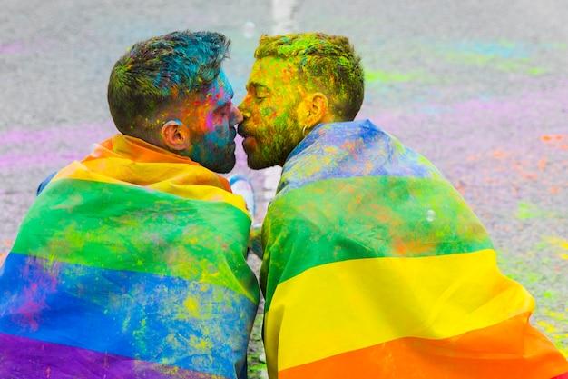 Zabrudzenie W Farbie Pary Homoseksualnej Całuje Zawinięte W Tęczową Flagę Na Paradzie Dumy Lgbt Darmowe Zdjęcia