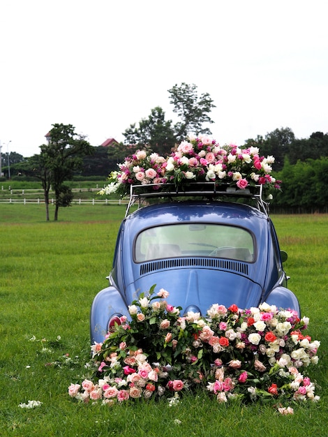 Zabytkowe samochody ozdobione kwiatami na polach trawiastych. Premium Zdjęcia