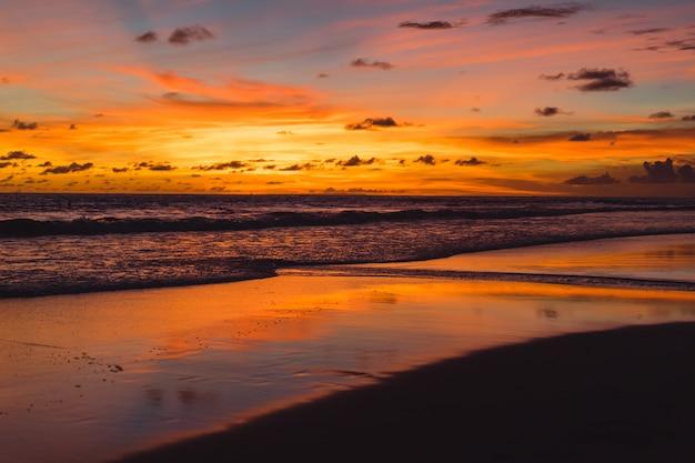 Zachód słońca nad oceanem. piękne jasne niebo, odbicie w wodzie, fale. Darmowe Zdjęcia