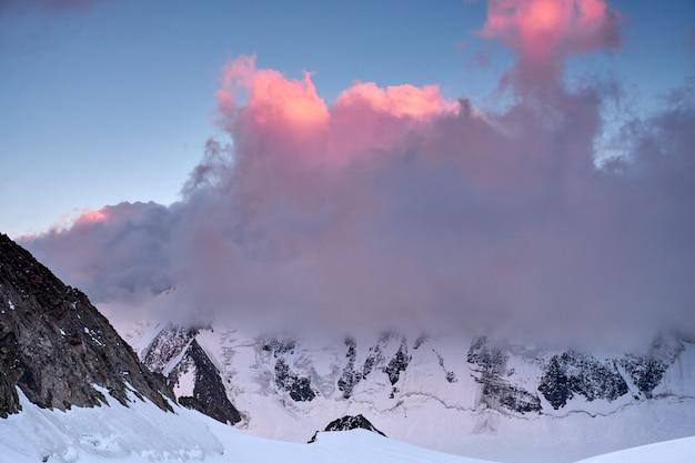 Zachód Słońca W Górach. Odbicie Czerwonego Słońca Na Szczytach Górskich śniegu I Chmur. Ałtaj, Rejon Belukha Premium Zdjęcia