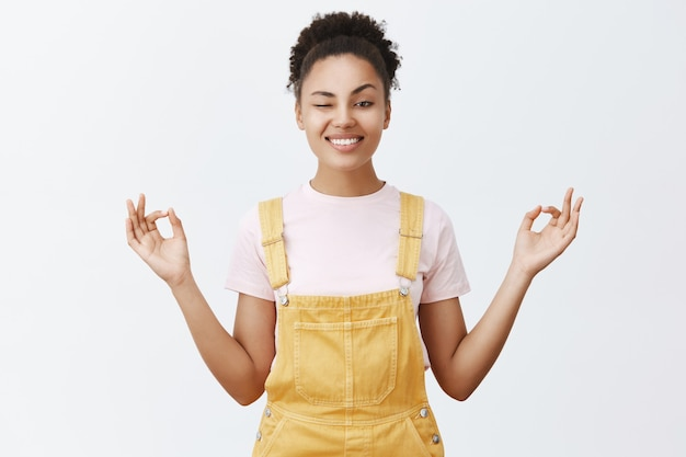 Zachowaj Spokój I Uwolnij Się Od Stresu Dzięki Medytacji. Radosna I Figlarna Stylowa Nowoczesna Afroamerykanka W żółtym Kombinezonie, Zerkająca Jednym Okiem I Szeroko Uśmiechnięta, Trzymająca Się Za Ręce W Pozie Zen Darmowe Zdjęcia
