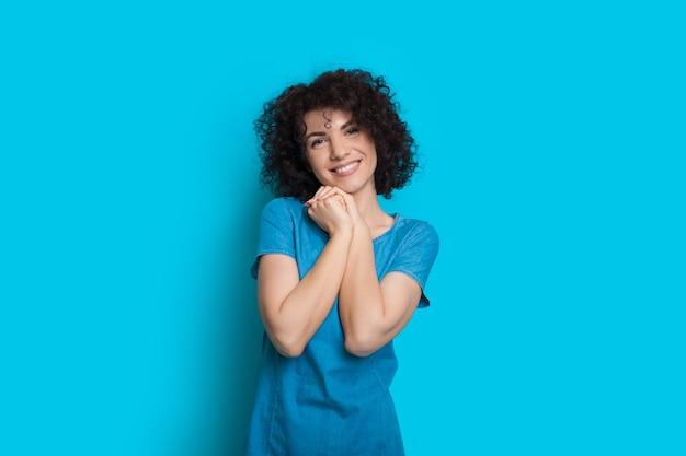 Zachwycająca Kaukaska Dama Z Czarnymi Kręconymi Włosami Patrzy W Kamerę I Uśmiecha Się Radośnie Premium Zdjęcia