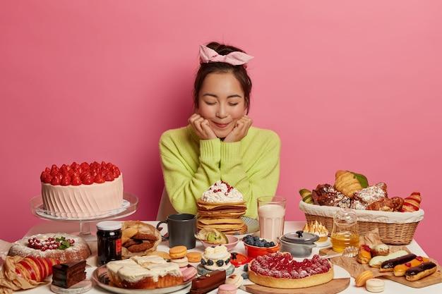Zachwycona Azjatka Nosi Opaskę I Zielony Sweter, Trzyma Podbródek, Ma Dobry Apetyt, Je Słodkie Jedzenie, Ciastka Owocowe, Przychodzi Na Przyjęcie Urodzinowe, Odizolowane Na Różowej ścianie Darmowe Zdjęcia