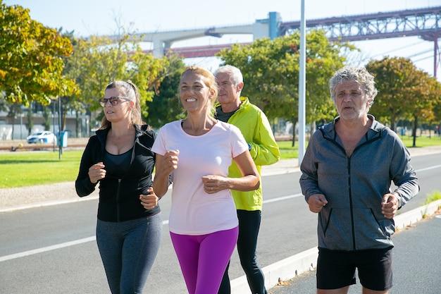 Zadowoleni I Zmęczeni Dojrzali Biegacze W Sportowych Ubraniach Biegają Na Zewnątrz, Trenują Do Maratonu, Cieszą Się Porannym Treningiem. Emeryci I Koncepcja Aktywnego Stylu życia Darmowe Zdjęcia