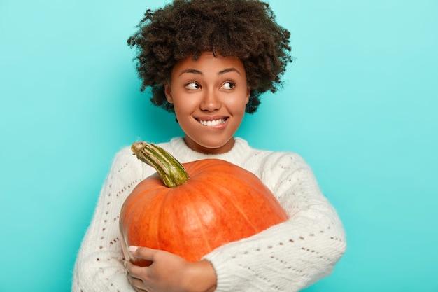 Zadowolona Afro Dziewczyna Obejmuje Dużą Pomarańczową Dynię, Gryzie Usta, Nosi Dzianinowy Biały Sweter, Ma Jesienny Nastrój, Patrzy Na Bok, Odizolowana Na Niebieskim Tle. Darmowe Zdjęcia