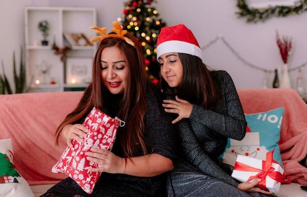 Zadowolona Córka I Matka Patrzą Na Prezent Matki Siedząc Na Kanapie Tyłem Do Siebie, Ciesząc Się świątecznymi W Domu Darmowe Zdjęcia