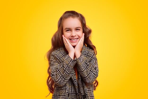 Zadowolona Dziewczyna W Ciepły Płaszcz Patrząc Na Kamery Premium Zdjęcia