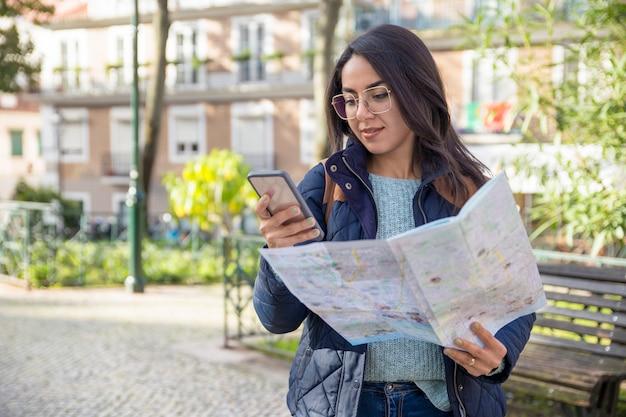 Zadowolona kobieta za pomocą papierowej mapy i smartphone na zewnątrz Darmowe Zdjęcia