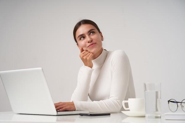 Zadowolona Młoda Ciemnowłosa ładna Kobieta Z Naturalnym Makijażem, Pochylająca Głowę Z Uniesioną Ręką I Patrząca Pozytywnie W Górę Z Radosnym Uśmiechem, Siedząca Na Białej ścianie Darmowe Zdjęcia