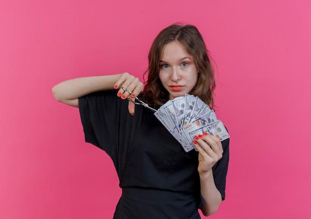 Zadowolona Młoda Słowiańska Fryzjerka W Mundurze, Trzymająca Pieniądze I Nożyczki, Próbująca Wyciąć Pieniądze Na Różowym Tle Z Miejscem Na Kopię Darmowe Zdjęcia