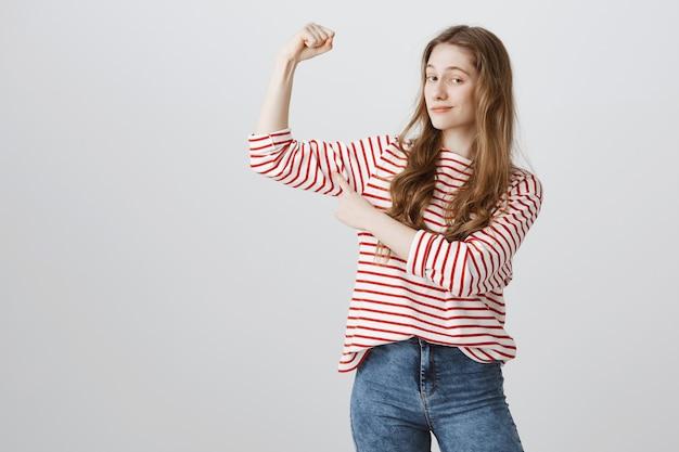 Zadowolona Nastolatka Napina Bicepsy I Jest Zadowolona Z Uśmieszku Darmowe Zdjęcia