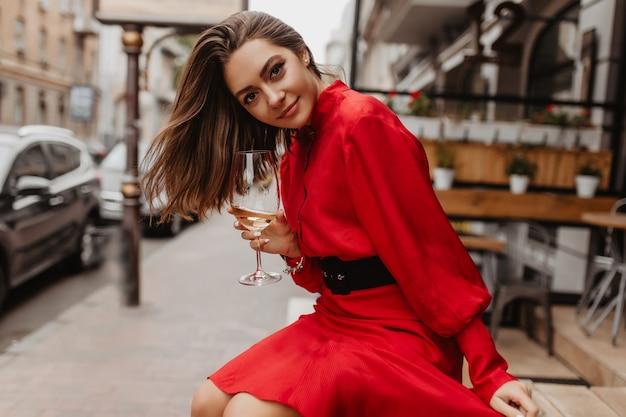 Zadowolona, Słodka Dziewczyna Uśmiecha Się Delikatnie. Czerwona Sukienka Dodaje Blasku Stylizacji Pani Pozującej Przy Lampce Wina Darmowe Zdjęcia