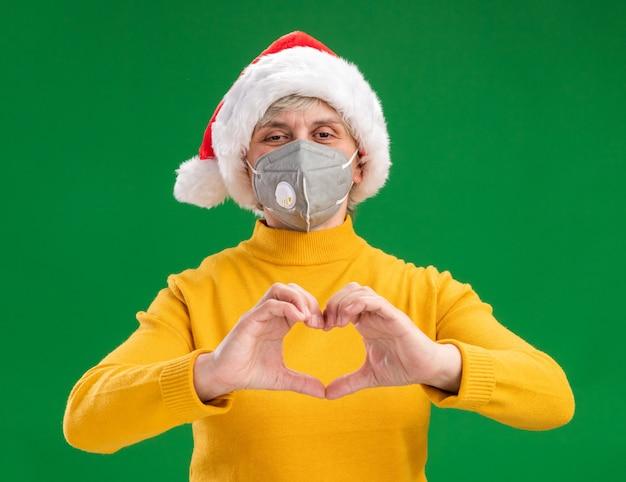 Zadowolona Starsza Kobieta W Kapeluszu Mikołaja W Masce Medycznej, Wskazując Znak Serca Na Białym Tle Na Zielonym Tle Z Miejsca Na Kopię Darmowe Zdjęcia