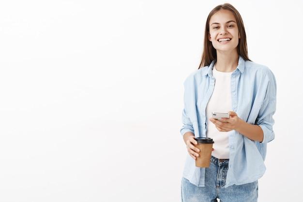Zadowolona Szczęśliwa Atrakcyjna Kaukaska Kobieta W Niebieskiej Bluzce Na Koszulce Trzymająca Papierowy Kubek Z Kawą I Telefon Komórkowy Uśmiechnięta Z Zachwytu Szczęśliwa Z Przerwy Podczas Pracy W Biurze Darmowe Zdjęcia