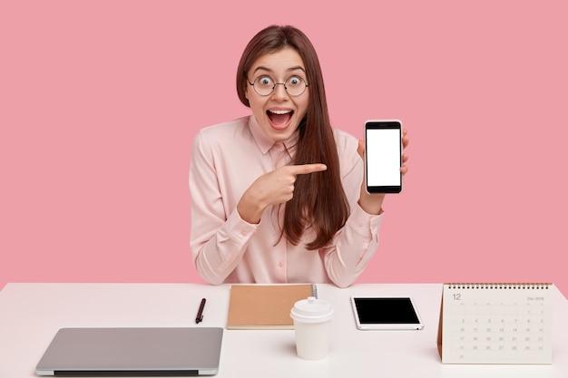 Zadowolona Szczęśliwa Kobieta Wskazuje Na Telefon Komórkowy Z Makietowym Ekranem, Ma Zdumiony Wyraz Twarzy, Jest Perfekcjonistą, Dąży Do Nieskazitelności Darmowe Zdjęcia
