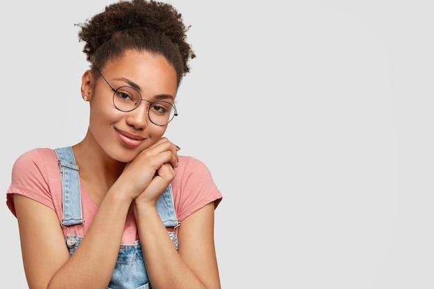 Zadowolona, Zachwycona Młoda Afroamerykanka O Ciemnej Skórze, Atrakcyjnym Wyglądzie, Trzyma Ręce Razem Pod Brodą, Nosi Okulary I Zwykłe Ubrania, Pozuje Na Białej ścianie Z Wolną Przestrzenią Darmowe Zdjęcia