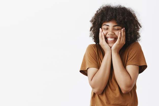 Zadowolona Zakochana Kobieta Z Afryki Ameryki Czuje Podekscytowanie I Uczucie, Które Podnosi Się I Dotyka Po Wspaniałej Randce W Romantycznym Miejscu, Trzymając Ręce Na Twarzy, Zamykając Oczy I Szeroko Się Uśmiechając Darmowe Zdjęcia