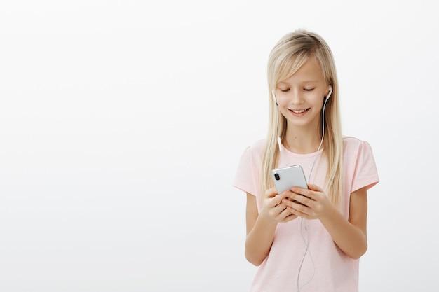 Zadowolone Kreatywne Dziecko Oglądające Filmy, Czekając Na Mamę. Portret Uroczej Młodej Dziewczyny Z Jasnymi Włosami, Słuchając Muzyki W Słuchawkach I Trzymając Smartfon, Uśmiechając Się Z Pozytywnej Wiadomości Darmowe Zdjęcia