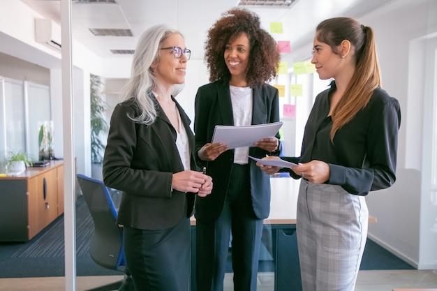 Zadowolone Młode Przedsiębiorczynie Omawiające Statystyki I Uśmiechnięte. Trzy Szczęśliwe Atrakcyjne Koleżanki Stojąc Z Papierami I Rozmawiając W Sali Konferencyjnej. Koncepcja Pracy Zespołowej, Biznesu I Zarządzania Darmowe Zdjęcia