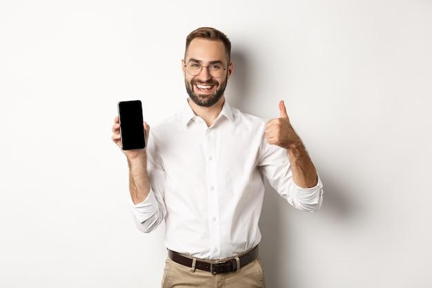 Zadowolony Biznesmen W Okularach, Pokazując Kciuki Do Góry I Pokazując Ekran Telefonu Komórkowego, Polecając Aplikację, Stojąc Na Białym Tle. Darmowe Zdjęcia