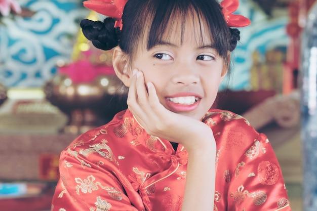 Zadowolony Chińczyk Nowy Rok 2018, ładna Azjatycka Dziewczyna W Chińskiej Sukience, Szanując Boga. Księżycowy Nowy Rok Lub święto Wiosny Jest Najważniejszym Z Tradycyjnych Chińskich świąt. Premium Zdjęcia