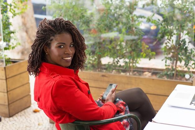 Zadowolony Kobiety Mienia Smartphone I Ono Uśmiecha Się Darmowe Zdjęcia