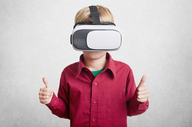 Zadowolony Mały Chłopiec Lubi Wirtualną Rzeczywistość, Nosi Słuchawki Vr Lub Okulary 3d, Pokazuje Znak Ok, Jako Zadowolony Z Efektu, Gra W Gry Online Na Białym Tle. Innowacyjna Technologia Premium Zdjęcia
