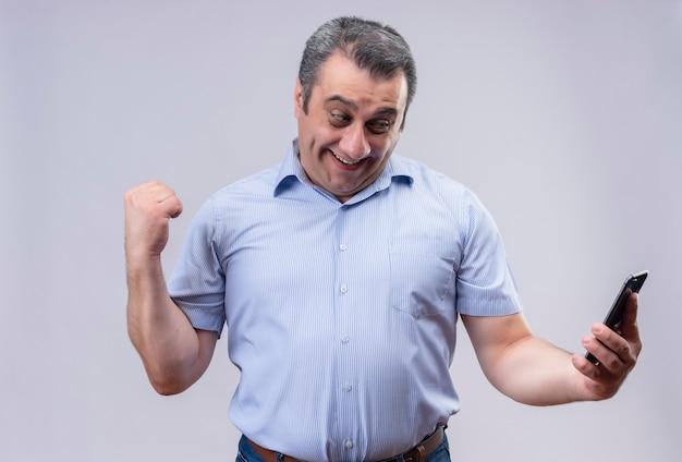 Zadowolony Mężczyzna W średnim Wieku Ubrany W Niebieską Koszulę W Pionowe Paski, Patrząc Na Swój Telefon Komórkowy I Pokazujący Zaciśniętą Pięść Z Gestem Ręki, Stojąc Darmowe Zdjęcia