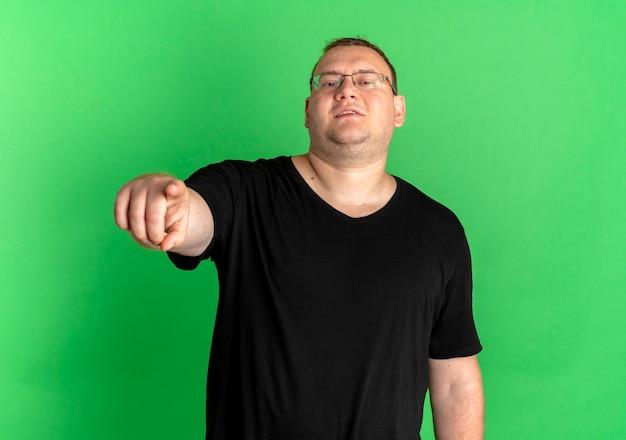 Zadowolony Mężczyzna Z Nadwagą W Okularach Na Sobie Czarną Koszulkę, Wskazując Palcem Uśmiechnięty Stojący Nad Zieloną ścianą Darmowe Zdjęcia