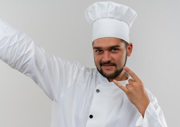 Zadowolony Młody Kucharz W Mundurze Szefa Kuchni Robi Rockowy Znak Wyciągając Rękę Obok Na Białym Tle Na Białej Przestrzeni Darmowe Zdjęcia