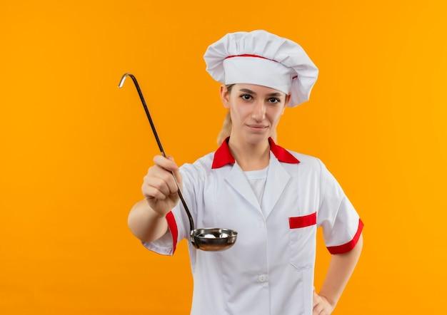 Zadowolony Młody ładny Kucharz W Mundurze Szefa Kuchni Wyciągający Chochlę Z Ręką Na Talii Odizolowany Na Pomarańczowej Przestrzeni Darmowe Zdjęcia