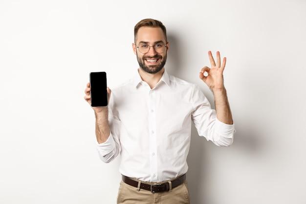 Zadowolony Młody Menedżer, Pokazujący Ekran Smartfona I Znak Ok, Polecający Aplikację, Stojący Na Białym Tle. Darmowe Zdjęcia