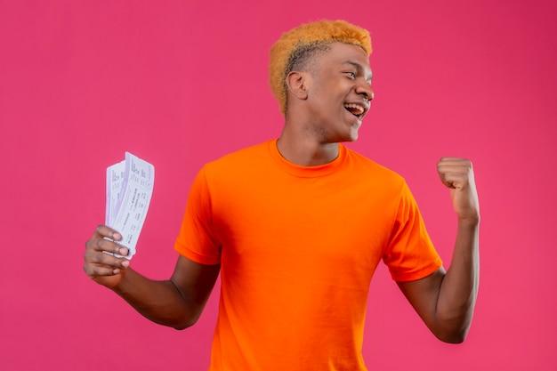 Zadowolony Młody Przystojny Chłopak Ubrany W Pomarańczową Koszulkę Trzymający Walizkę Podróżną Uśmiechnięty Szczęśliwy I Podekscytowany Podnosząc Pięść, Ciesząc Się Swoim Sukcesem Stojącym Nad Różową ścianą Darmowe Zdjęcia