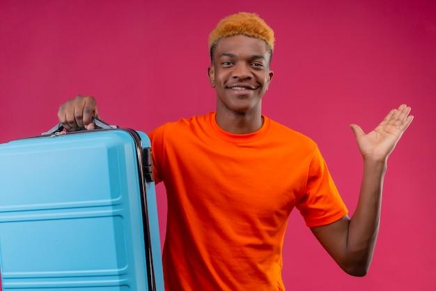 Zadowolony Młody Przystojny Chłopak Ubrany W Pomarańczowy T-shirt, Trzymając Walizkę Podróżną, Uśmiechnięty Szczęśliwy I Pozytywny Z Podniesioną Ręką Stojącą Nad Różową ścianą Darmowe Zdjęcia