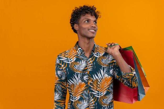 Zadowolony Młody Przystojny Ciemnoskóry Mężczyzna Z Kręconymi Włosami W Koszulce Z Nadrukiem W Liście Uśmiecha Się Trzymając Torby Na Zakupy, Stojąc Na Pomarańczowym Tle Darmowe Zdjęcia
