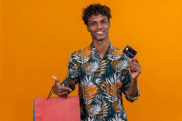 Zadowolony Młody Przystojny Ciemnoskóry Mężczyzna Z Kręconymi Włosami W Liściach Koszulę Z Nadrukiem Uśmiechnięte Torby Na Zakupy Pokazujące Kartę Kredytową Stojąc Na Pomarańczowym Tle Darmowe Zdjęcia