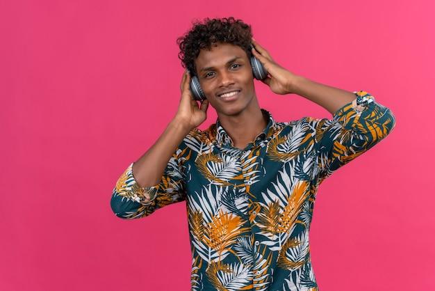 Zadowolony Przystojny Ciemnoskóry Mężczyzna Z Kręconymi Włosami W Koszulce Z Nadrukiem Liści W Słuchawkach, Słuchający Muzyki Na Różowym Tle Darmowe Zdjęcia