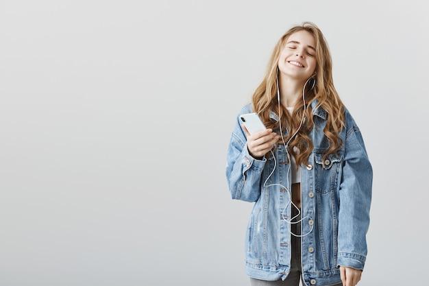 Zadowolony Szczęśliwy Blond Dziewczyna Ciesząc Się Niesamowitą Nową Piosenką W Słuchawkach, Słuchając Muzyki, Trzymając Smartfon Darmowe Zdjęcia