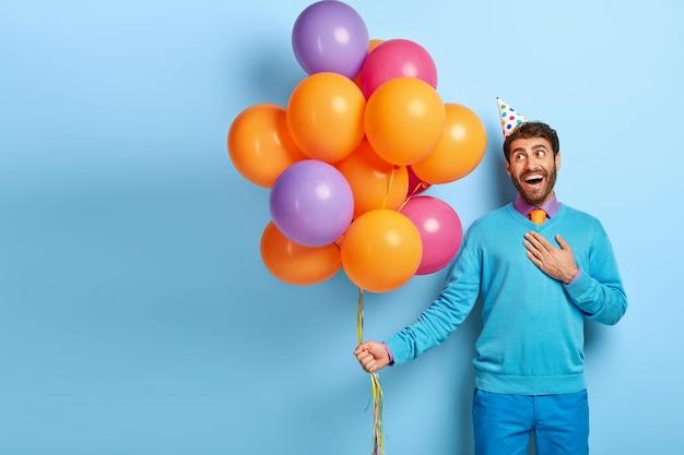 Zadowolony, Zachwycony Facet Z Urodzinową Czapką I Balonami Pozuje W Niebieskim Swetrze Darmowe Zdjęcia