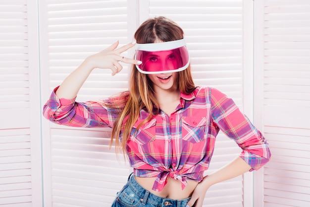 Zadumana Nastoletnia Dziewczyna Jest Ubranym W Kratkę Koszula I Baseball Nakrętkę Przyglądającą W Myślach Nad Różowym Tłem Up Premium Zdjęcia