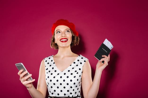 Zadumana Uśmiechnięta Imbirowa Kobieta W Smokingowym Mienia Paszporcie Z Biletami I Smartphone Podczas Gdy Patrzejący Up Nad Menchiami Darmowe Zdjęcia