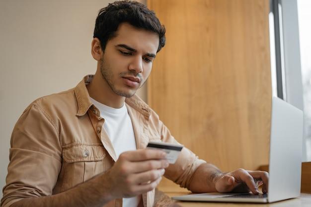Zadumany Indianin Używa Laptop, Trzyma Kartę Kredytową, Robi Zakupy Online. Azjatycki Biznesmen Sprawdza Saldo Konta, Pracuje Od Domu Premium Zdjęcia