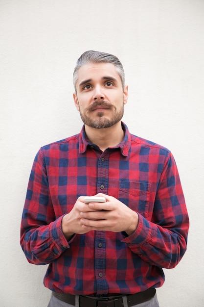 Zadumany Mężczyzna Trzyma Smartphone I Przyglądającego Up Darmowe Zdjęcia