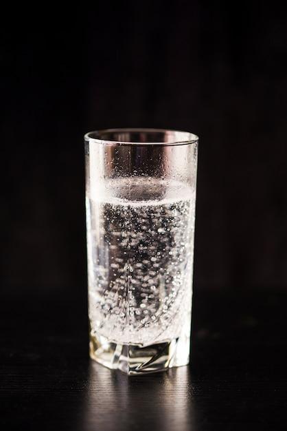 Zagazowana Woda W Szkle Na Czarnym Stole I Czarnym Tle. Premium Zdjęcia