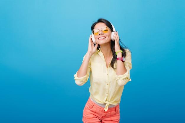 Zainspirowana Azjatycka Modelka W Różowym Zegarku I Zielonej Bransoletce Słuchająca Muzyki. Kryty Zdjęcie Ekstatycznej łacińskiej Dziewczyny W Pomarańczowych Okularach Przeciwsłonecznych, Dotykając Słuchawek I Uśmiechając Się. Darmowe Zdjęcia