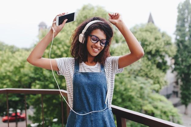 Zainspirowana Czarna Dziewczyna Z Modną Kręconą Fryzurą Tańczy Na Balkonie Z Drzewami Darmowe Zdjęcia