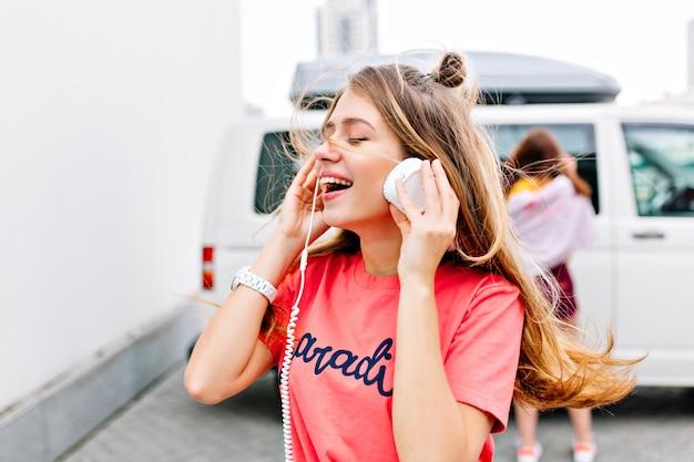 Zainspirowana Dziewczyna Z Modną Fryzurą W Stylowej Różowej Koszuli, Ciesząca Się Dobrą Piosenką Z Uśmiechem I Zamkniętymi Oczami Darmowe Zdjęcia