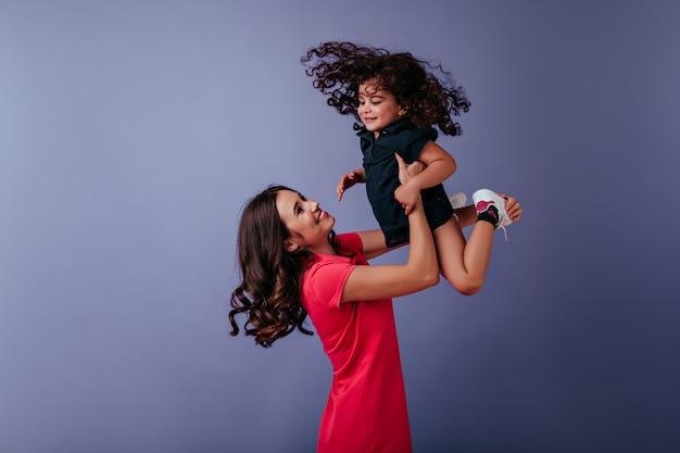 Zainspirowana Kręcona Kobieta Bawi Się Z Młodszą Siostrą. Cudowna Młoda Mama Spędzająca Wolny Czas Z Córką. Darmowe Zdjęcia
